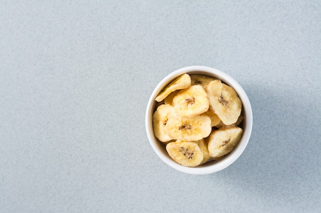 Chips De Banane Au Four Dans Un Bol Blanc Sur La Table. Fast Food. Copiez L'espace. Vue De Dessus Photo Premium