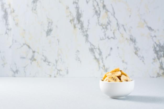 Chips De Banane Dans Un Bol Blanc Sur La Table. Fast Food. Copier L'espace Photo Premium