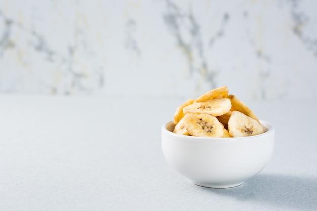 Chips De Banane Dans Un Bol Sur La Table. Fast Food. Copier L'espace Photo Premium