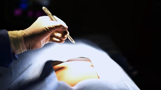 Chirurgien de l'équipe au travail en salle d'opération. lumière chirurgicale dans la salle d'opération. Photo Premium