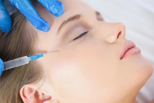 Chirurgien faisant l'injection sur les pattes d'oie sur femme calme couchée Photo Premium