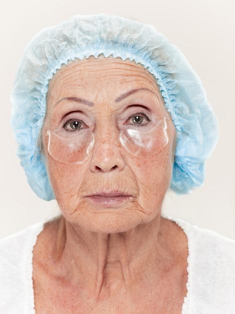 Chirurgien Faisant Une Vérification De La Peau D'une Femme D'âge Moyen Avant Une Chirurgie Plastique Photo gratuit