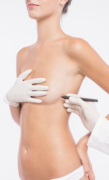 Chirurgien plasticien dessinant des lignes sur le corps de la femme Photo gratuit