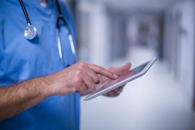 Chirurgien De Sexe Masculin à L'aide De Tablette Numérique En Salle D'opération Photo gratuit