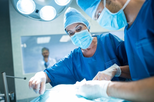 Les chirurgiens qui pratiquent l'exploitation en salle d'opération Photo gratuit