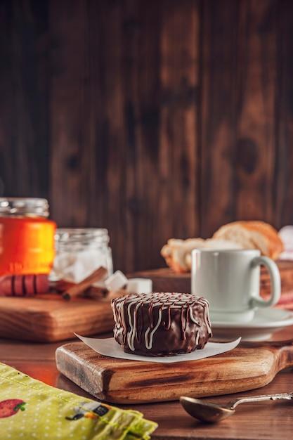 Chocolat Biscuit Au Miel Brésilien Recouvert Sur La Table En Bois Avec Café Et Abeille - Pao De Mel Photo Premium
