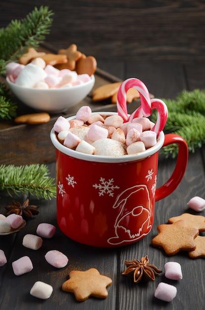 Chocolat chaud aux guimauves et épices sur un fond en bois foncé. composition de noël Photo Premium