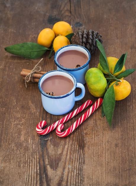 Chocolat Chaud Dans Des Tasses En Métal émaillé, Des Mandarines Fraîches, Des Bâtons De Cannelle, Des Pommes De Pin Et Des Cannes De Bonbon Photo Premium