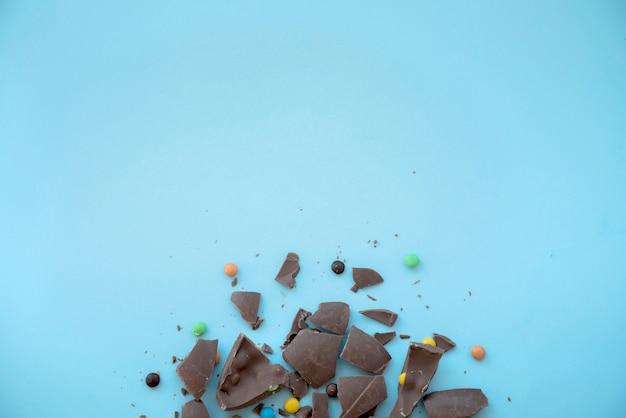 Chocolat craquelé avec des bonbons sur la table bleue Photo gratuit