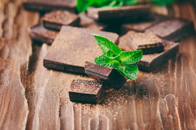 Chocolat Noir Et Menthe Verte Sur La Table En Bois, Mise Au Point Sélective Et Image Tonique Photo Premium