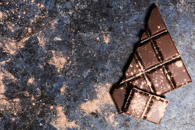 Chocolat à plat recouvert de cacao sur une table de grunge Photo gratuit