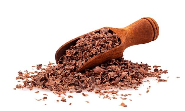 Chocolat râpé, tas de chocolat en poudre avec une cuillère en bois, isolé sur blanc, gros plan Photo Premium