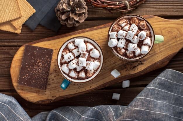 Des chocolats chauds à plat avec des guimauves et une tablette de chocolat Photo gratuit