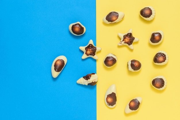Chocolats Sous Forme De Coquillages Et Coquillages Sur Fond Jaune Et Bleu. Photo Premium