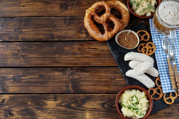 Chope de bière, bretzels et saucisses sur fond de table en bois en vue de dessus Photo Premium