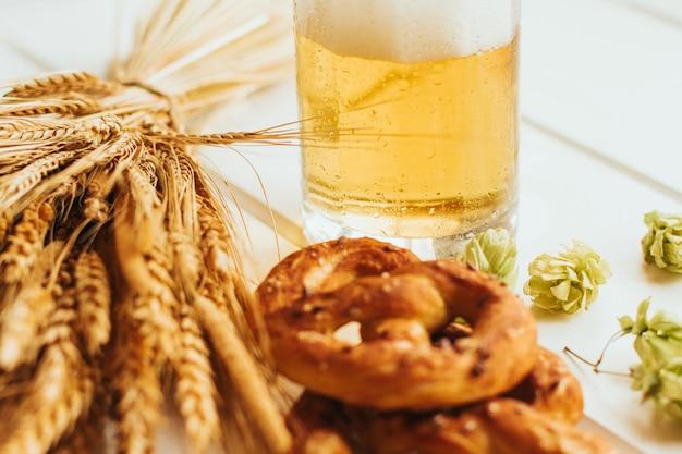 Chope de bière, cônes de houblon et bretzels sur une table en bois blanche. Photo Premium