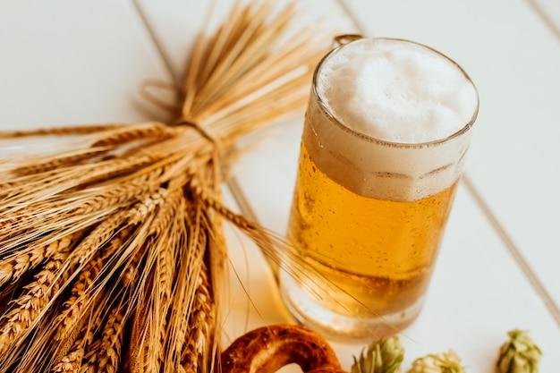 Chope de bière, cônes de houblon, épillets de seigle et de blé et bretzels sur bois blanc Photo Premium