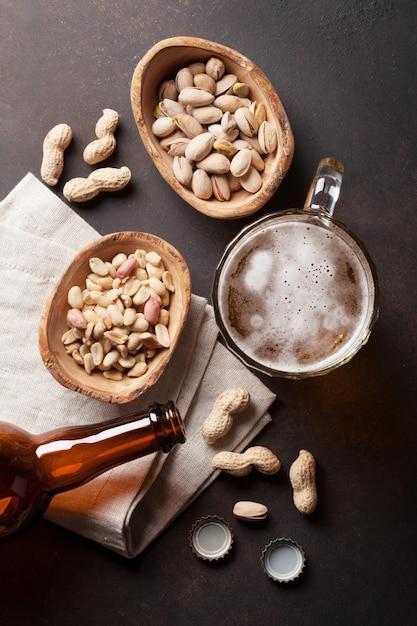 Chope à bière lager, bouteille et collations sur une table en pierre Photo Premium