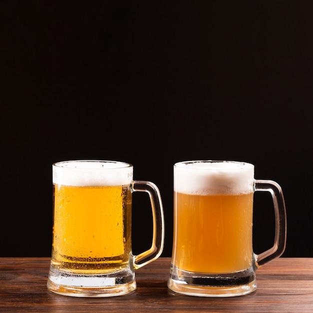 Chope de bière avec mousse sur planche de bois Photo gratuit