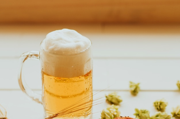 Chope de bière avec de la mousse sur une table blanche Photo Premium