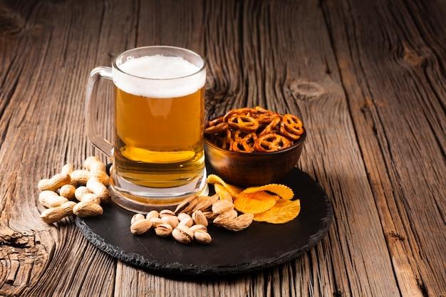 Chope de bière à la pistache et des collations sur une planche de bois Photo gratuit