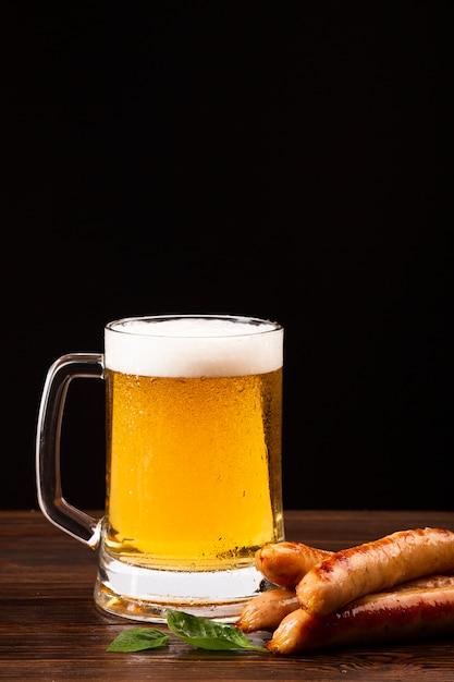 Chope de bière et saucisses sur planche de bois Photo gratuit