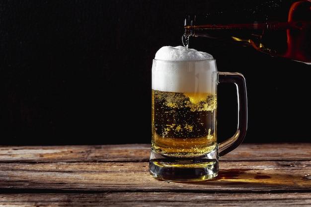 Chope de bière sur une table en bois Photo Premium