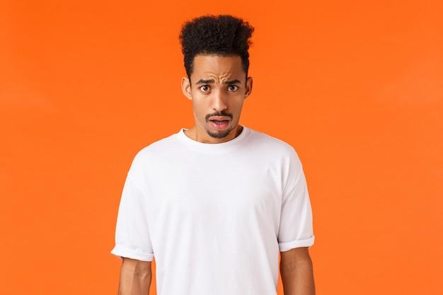 Choqué Et étonné, Sans Voix Jeune Homme Afro-américain Avec Moustache, Coiffure Afro, Grincement De Dégoût, Scène Horrible, Haletant Bouche Ouverte Confus Et Frustré, Orange Photo Premium