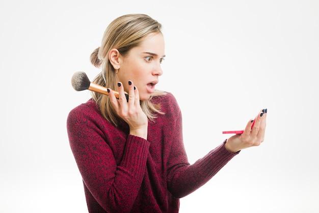 Choqué femme regardant dans un petit miroir Photo gratuit