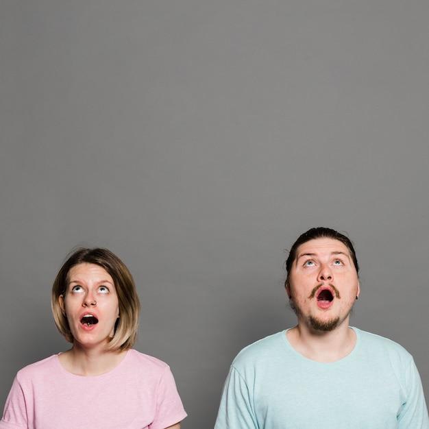 Choqué jeune couple avec la bouche ouverte levant les yeux contre un mur gris Photo gratuit