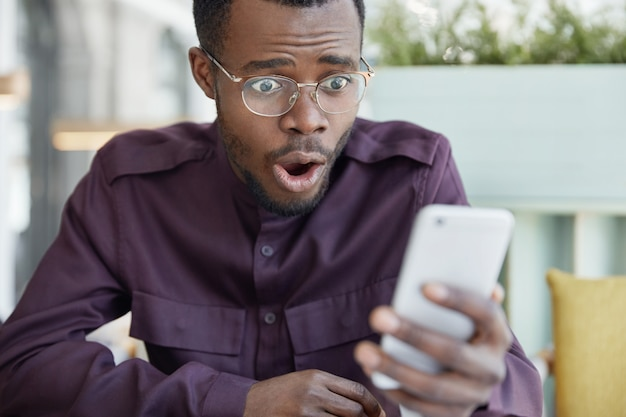 Choqué, Jeune Homme à La Peau Sombre à Lunettes Surpris Comme Reçoit Un Reçu De Facture Sur Un Téléphone Mobile, Stressé Pour Lire Des Nouvelles Choquantes Photo gratuit
