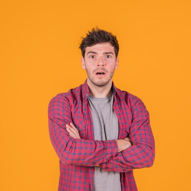 Choqué jeune homme avec son bras croisé contre un fond orange Photo gratuit
