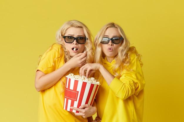 Choqué Jeunes Mannequins Femmes Dans Des Lunettes 3d Mangeant Du Pop-corn, Un Film Effrayant. Isolé Sur Mur Jaune Photo Premium