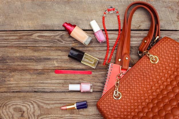 Choses du sac à main ouvert. sac à main féminin sur fond de bois. image tonique. Photo Premium