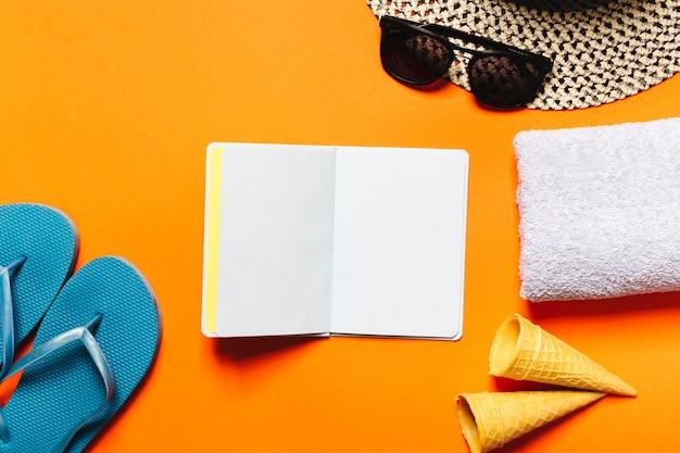 Choses station d'été et cahier sur fond coloré Photo gratuit