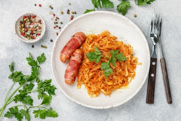 Chou cuit avec des carottes, des oignons et des tomates et des saucisses au bacon avec du persil et des épices Photo Premium