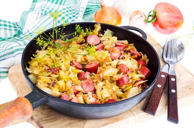 Chou frit avec des saucisses fumées dans une casserole Photo Premium