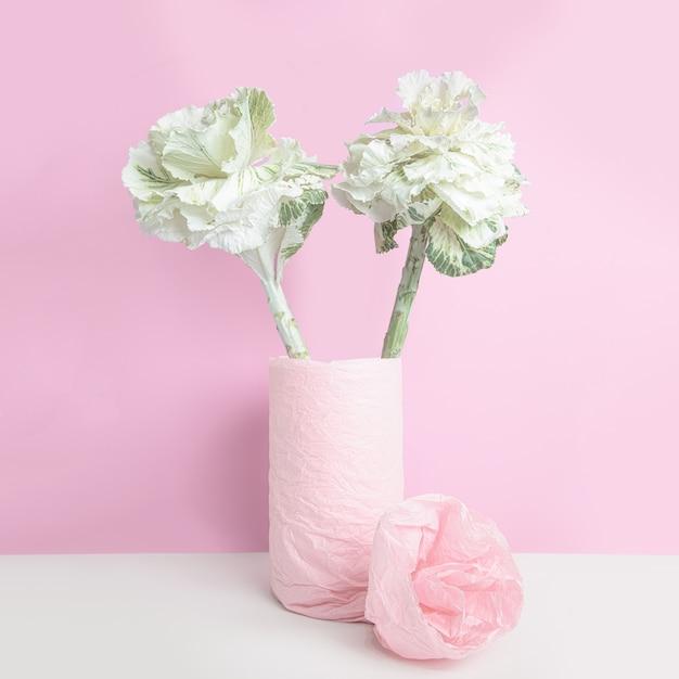 Chou Ornemental Dans Un Vase, Enveloppé De Papier Rose Sur Mur Rose Photo gratuit