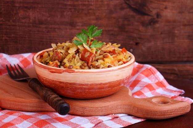 Choucroute aux saucisses et lentilles dans un bol en argile Photo Premium