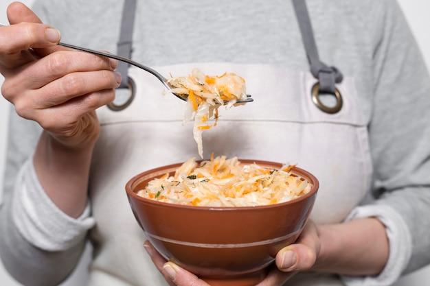 Choucroute sur une fourchette sur une assiette dans les mains d'une femme. Photo Premium
