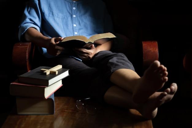 La chrétienne s'assit pour lire la bible sur une chaise en bois Photo gratuit