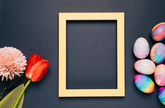 Chrysanthème; Tulipe Et Oeufs De Pâques Peints Avec Un Cadre Vide Jaune Sur Fond Noir Photo gratuit