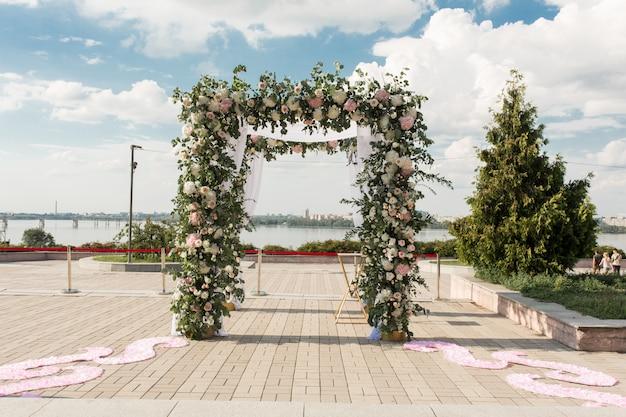 Un chuppah festif décoré de fleurs fraîches pour une cérémonie de mariage en plein air Photo Premium