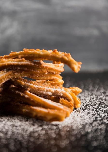 Churros close-up délicieux sur une table avec du sucre floue Photo gratuit