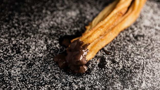 Churros haute vue trempés dans du chocolat Photo gratuit