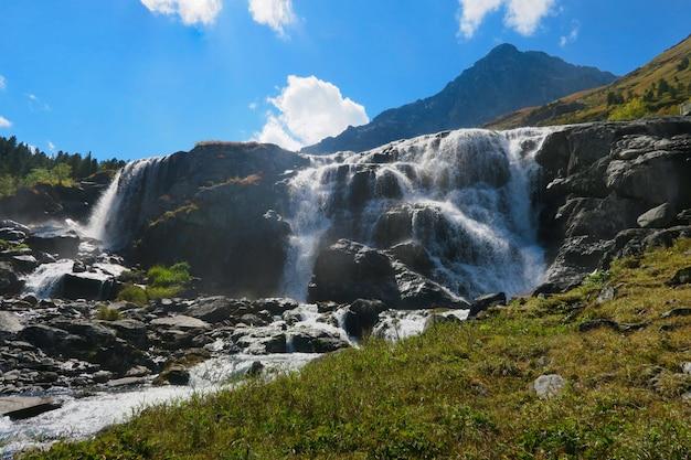 Chute d'eau en journée ensoleillée. montagnes de l'altaï, sibérie, russie Photo Premium