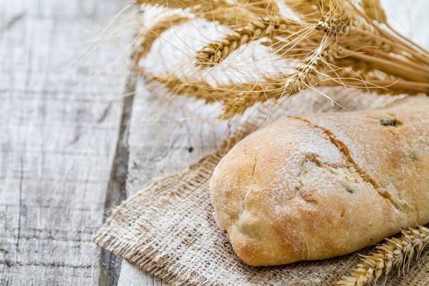 Ciabatta, blé, fond de bois rustique Photo Premium