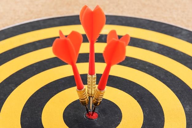 Une cible avec trois flèches de fléchettes frappant le bullseye Photo gratuit