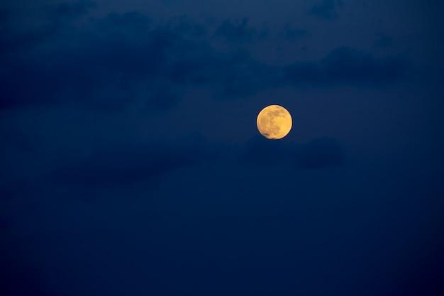 Ciel bleu foncé avec la pleine lune et les nuages Photo Premium