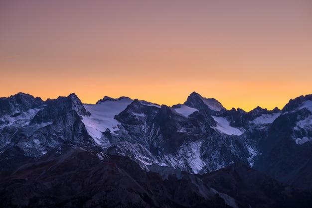 Ciel coloré au crépuscule au-delà des glaciers sur les majestueux sommets du massif des écrins (4101 m), france. téléphoto vue de loin en haute altitude. ciel orange clair. Photo Premium